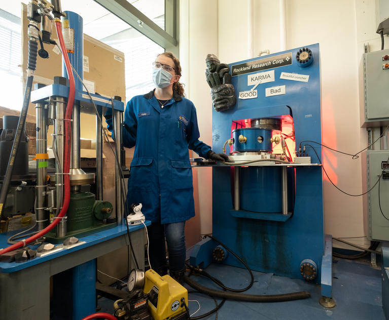 """Fourth-year graduate student Kelly Powderly standing with """"Karma,"""" the Cava Lab's high-Pressure, high-Temperature apparatus."""